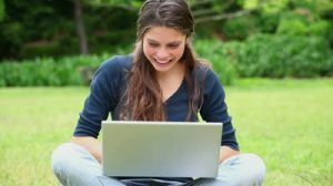 stock-footage-happy-woman-typing-on-her-laptop-in-a-park