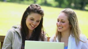 stock-footage-happy-young-women-using-a-laptop-in-a-park