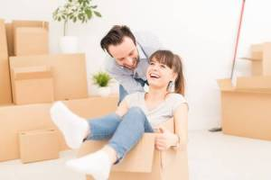 73650962-young-couple-people-have-fun-while-moving-to-a-new-apartment-boy-pushes-box-with-the-girl-happy-peop
